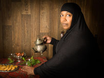 Oriental tea and dates. Smiling muslim woman pouring mint tea the traditional way Stock Photo