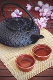 Oriental tea. Oriental inspired elements, like a typical iron teapot, tea cups, bamboo sheet, sakura or cherry blossom and a paper umbrella, combining elements Stock Photography