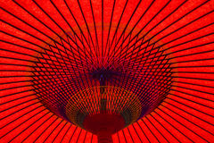 Oriental umbrella. Red oriental paper umbrella open in bright sunlight Royalty Free Stock Photos