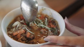 Oriental uzbek soup lagman - Central Asian cuisine. Female hands stir hot soup with a spoon, close-up stock video footage