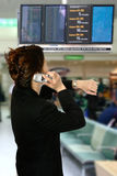 Oriental woman at airport. Asian businesswoman on her cellphone while looking at her watch, in the arrival/departure hall of the airport. Concept of time stock photography