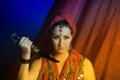 Oriental woman in red with a knife Stock Image