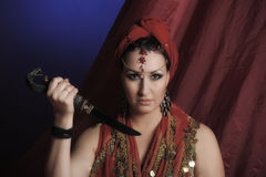 Oriental woman in red with a knife Royalty Free Stock Image