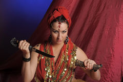 Oriental woman in red with a knife Stock Photo