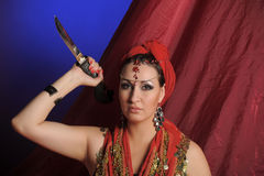 Oriental woman in red with a knife Royalty Free Stock Images