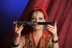Oriental woman in red with a knife Stock Photos