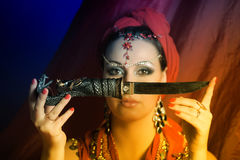 Oriental woman in red with a knife Stock Photography