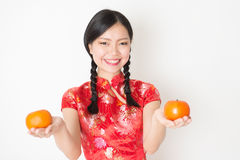 Oriental woman in red qipao holding mandarin orange Stock Images