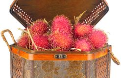 Oriental Woven Rattan Basket filled with Rambutan Fruits. Oriental Woven Rattan Basket on White Back Ground filled with Rambutan Fruits Stock Image