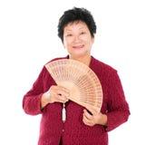 Orientalische ältere Frau mit chinesischem Gebläse Stockfoto