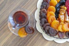 Orientalische Bonbontrockenfrüchte und -nüsse der türkischen Freude in einer Holzkiste mit türkischem Tee lizenzfreies stockfoto