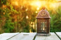 Orientalische Laterne der Weinlese über Holztisch draußen Stockfotografie