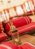 Orientalischer Aufenthaltsraum mit goldener Laterne und hölzernen Aufenthaltsraumsitzen mit Seidenkissen lizenzfreies stockbild
