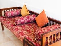 Orientalisk soffa med kuddar av burgundy färg royaltyfria bilder