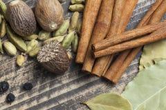Orientaliska indiska kryddor ryktar curcuma för kardemumma för paprikamuskotnötchili kanelbrun på tappningträ Royaltyfri Bild