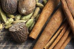 Orientaliska indiska kryddor ryktar curcuma för kardemumma för paprikamuskotnötchili kanelbrun på tappningträ Royaltyfria Bilder