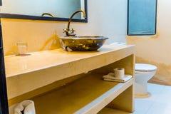Orientaliskt badrum med en färgad orange vägg Arkivbilder