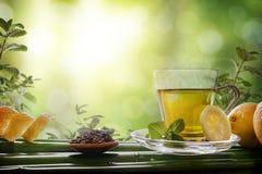 Orientaliskt grönt te med mintkaramellen och citroner på bambuframdel Arkivbilder