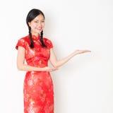 Orientalna dziewczyna w czerwonej qipao ręce pokazuje coś Obrazy Stock