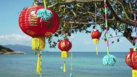 Orientalni dekoracyjni lampiony, czerwony chińczyk zaświecają obwieszenie na drzewie plażą na dennym tle 3840x2160 zbiory wideo