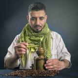 Orientalny mężczyzna w tradycyjnej krajowej arab sukni, zgrzytnięcie kawa groszkuje w starym miedzianym kawowym ostrzarzu obraz stock