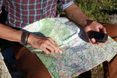 Orientation during a hike. A young man holds a map and a gps device in his hands Royalty Free Stock Photos