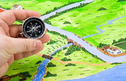 Orientation of the map in the journey. Compass in hand, and orientation on the map of the journey Stock Image