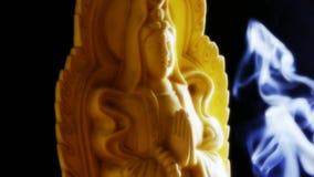 Oriente la estatua de Buda, incienso ardiente llenado hollín del humo almacen de video