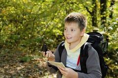 orienteering在森林里的微笑的男孩 库存照片