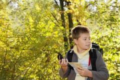 orienteering在森林里的男孩 免版税库存照片