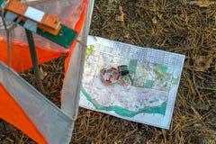 orienteering Compás, mapa, prisma del punto de control y composter para orienteering en el bosque en agujas caidas del otoño Imagenes de archivo