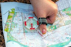 Orienteering. Compass and topographic map. The athlete uses navigation equipment for orienteering. The concept. Orienteering. Compass and topographic map. The Stock Photography