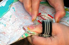 Orienteering. Compass and topographic map. The athlete uses navigation equipment for orienteering. The concept. Orienteering. Compass and topographic map. The royalty free stock image