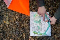 orienteering Compasso, mapa, prisma do ponto de verificação na floresta em agulhas caídas do outono O conceito fotos de stock royalty free