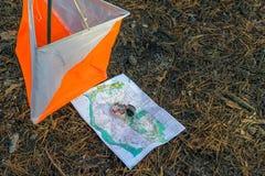 orienteering Compasso, mapa, prisma do ponto de verificação na floresta em agulhas caídas do outono O conceito fotografia de stock