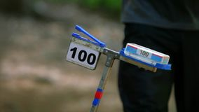 Orienteering training run. Sportsman or sportswoman come to electronical  checkpoint use chip.