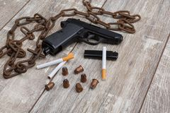 Orienteringen av en pistol, scatteed kassetter, cigaretter, en tändare, en hopfällbar kniv och en rostig kedja royaltyfria foton
