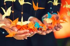 Origâmi do papel colorido sob a forma dos guindastes que penduram em um st Imagens de Stock Royalty Free
