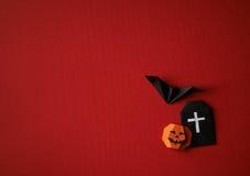 Origâmi dos símbolos de Dia das Bruxas em um fundo vermelho Foto de Stock