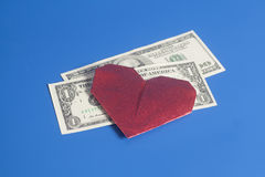 Origâmi e notas de dólar de papel vermelhos do coração no fundo azul Foto de Stock Royalty Free