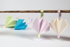Origami伞和晒衣绳概念 免版税库存图片
