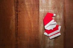 Origami圣诞老人在木背景的纸工艺 库存照片