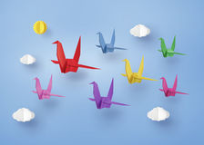 Origami在与clound的蓝天做了五颜六色的纸鸟飞行 免版税图库摄影