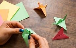 Origami工艺,孩子的工艺品 手工制造 在木桌上的手 库存图片