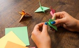 Origami工艺,孩子的工艺品 手工制造 在木桌上的手 图库摄影