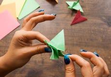Origami工艺,孩子的工艺品 手工制造 在木桌上的手 免版税库存图片