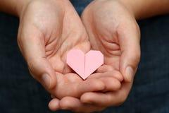 Origami心脏在手上 库存图片
