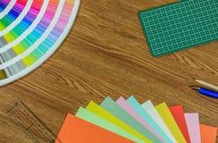 Origami裱糊,五颜六色的纸,切开席子和铅笔在木桌上 免版税库存图片