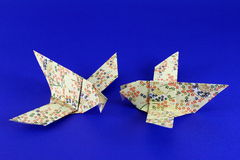 Origami birds. Two origami pigeons or doves made with Japanese folding paper on a blue background royalty free stock image