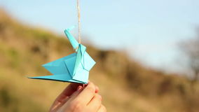 Origami, the art of origami. Origami crane. Small figures of origami cranes. Paper birds blue and sky blue. Small figure origami crane swaying in the wind. Two stock video footage